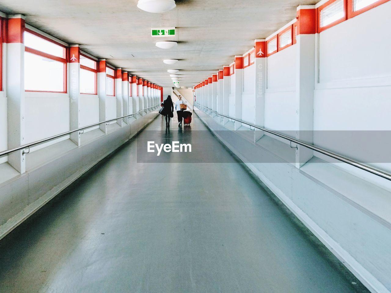 People Walking In Illuminated Corridor