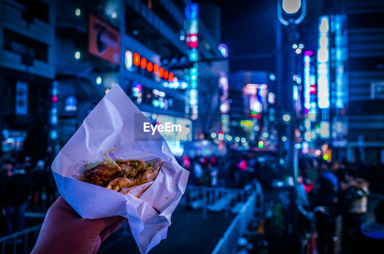 Cropped Image Of Hand Holding Burger In City At Night