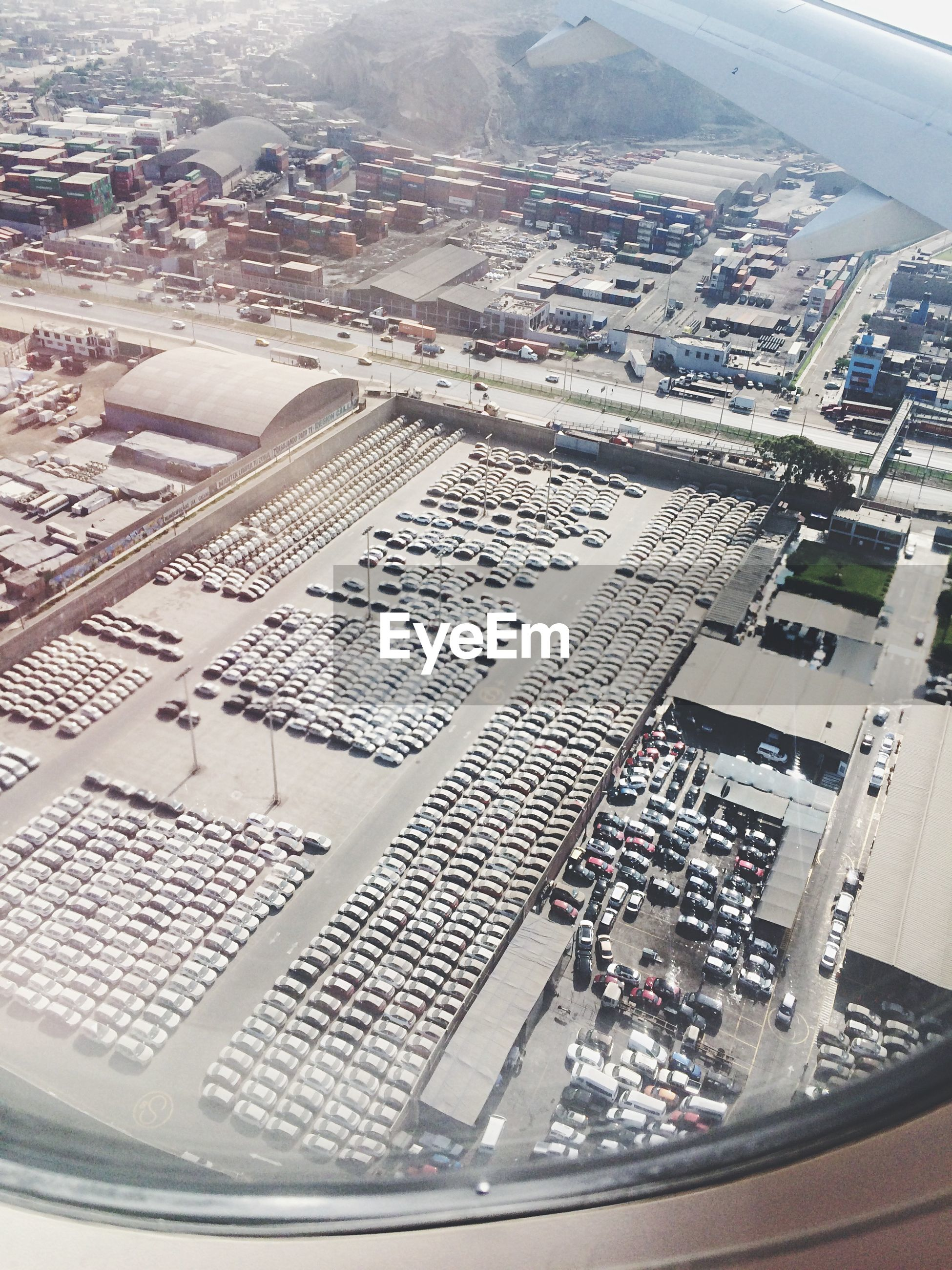 Tilt shift image of cars in parking lot seen through airplane window