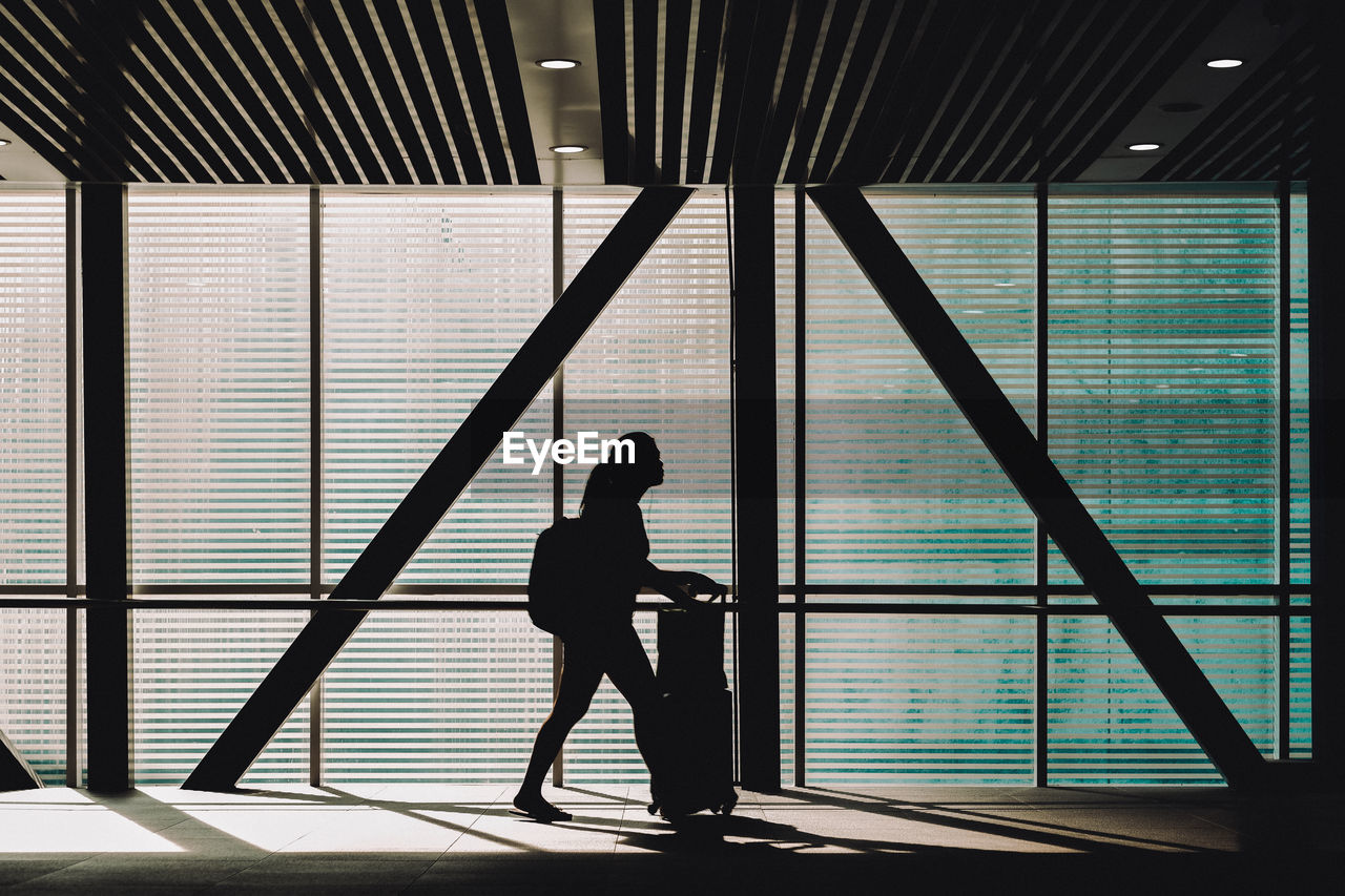 Side View Of Silhouette Teenage Girl Walking At Airport