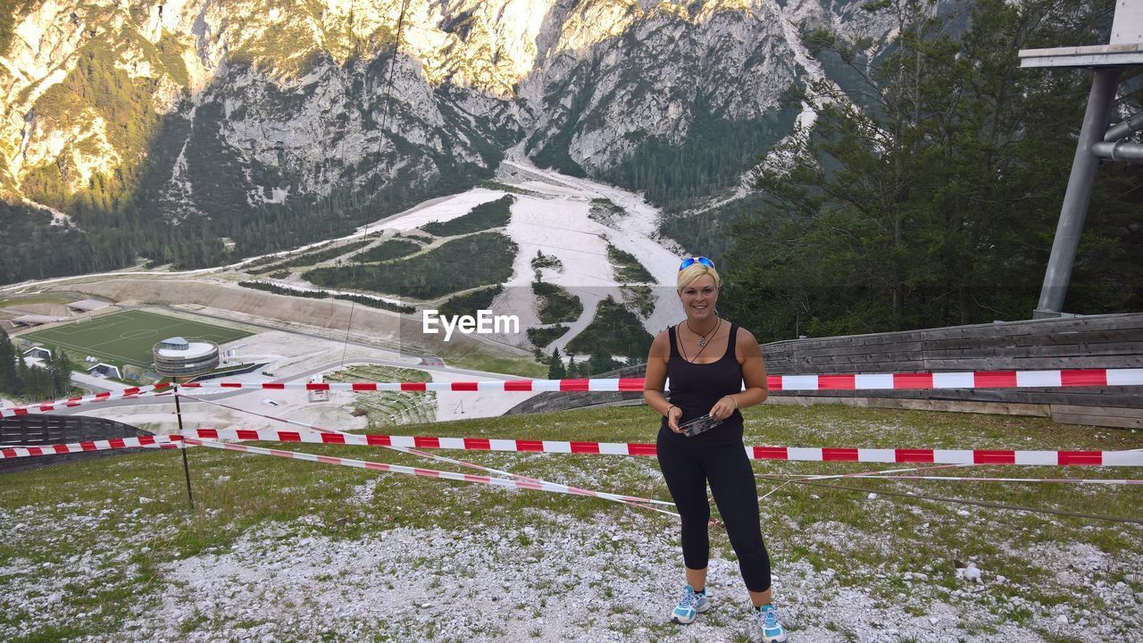 Full length portrait of woman standing by cordon tapes on mountain during winter