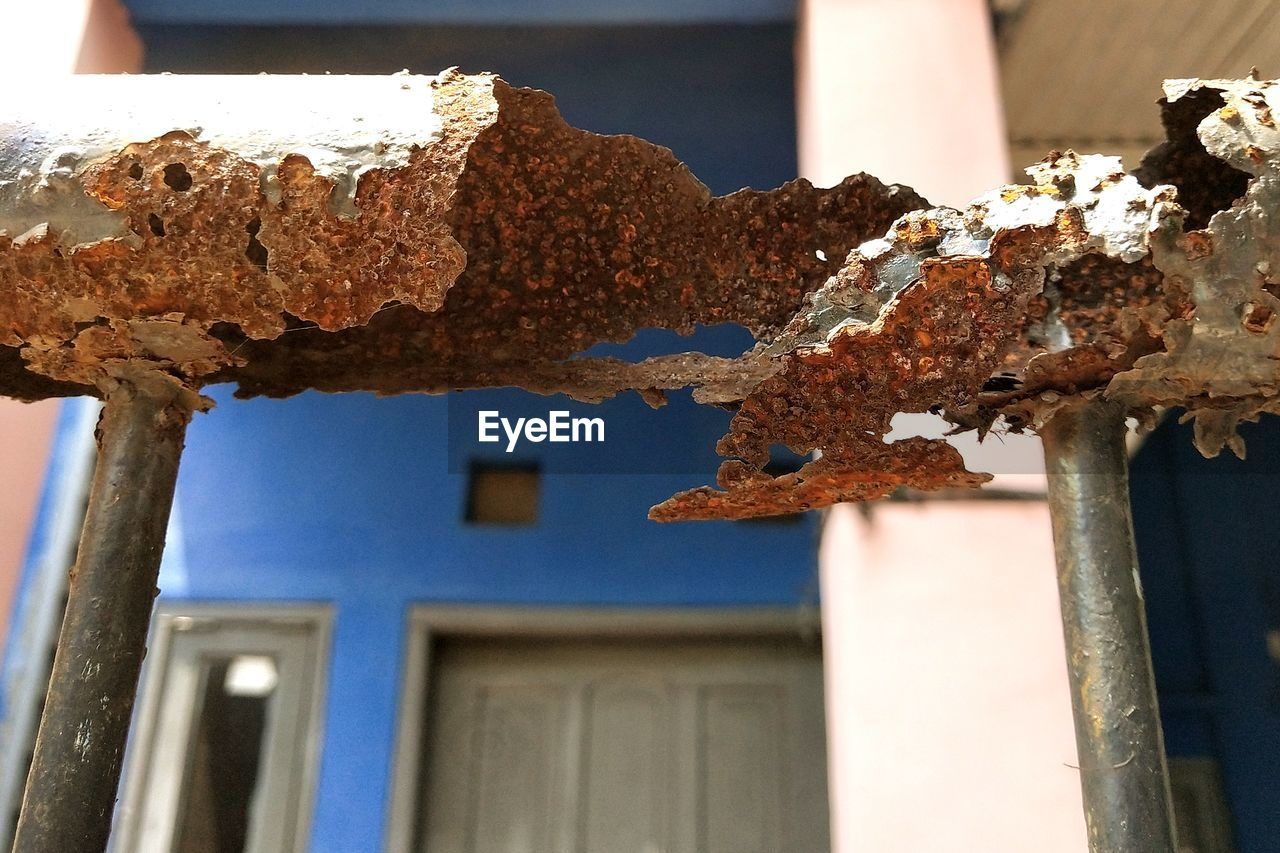 focus on foreground, rusty, day, close-up, built structure, no people, metal, architecture, weathered, building, damaged, building exterior, old, outdoors, low angle view, nature, run-down, abandoned, house, decline, deterioration