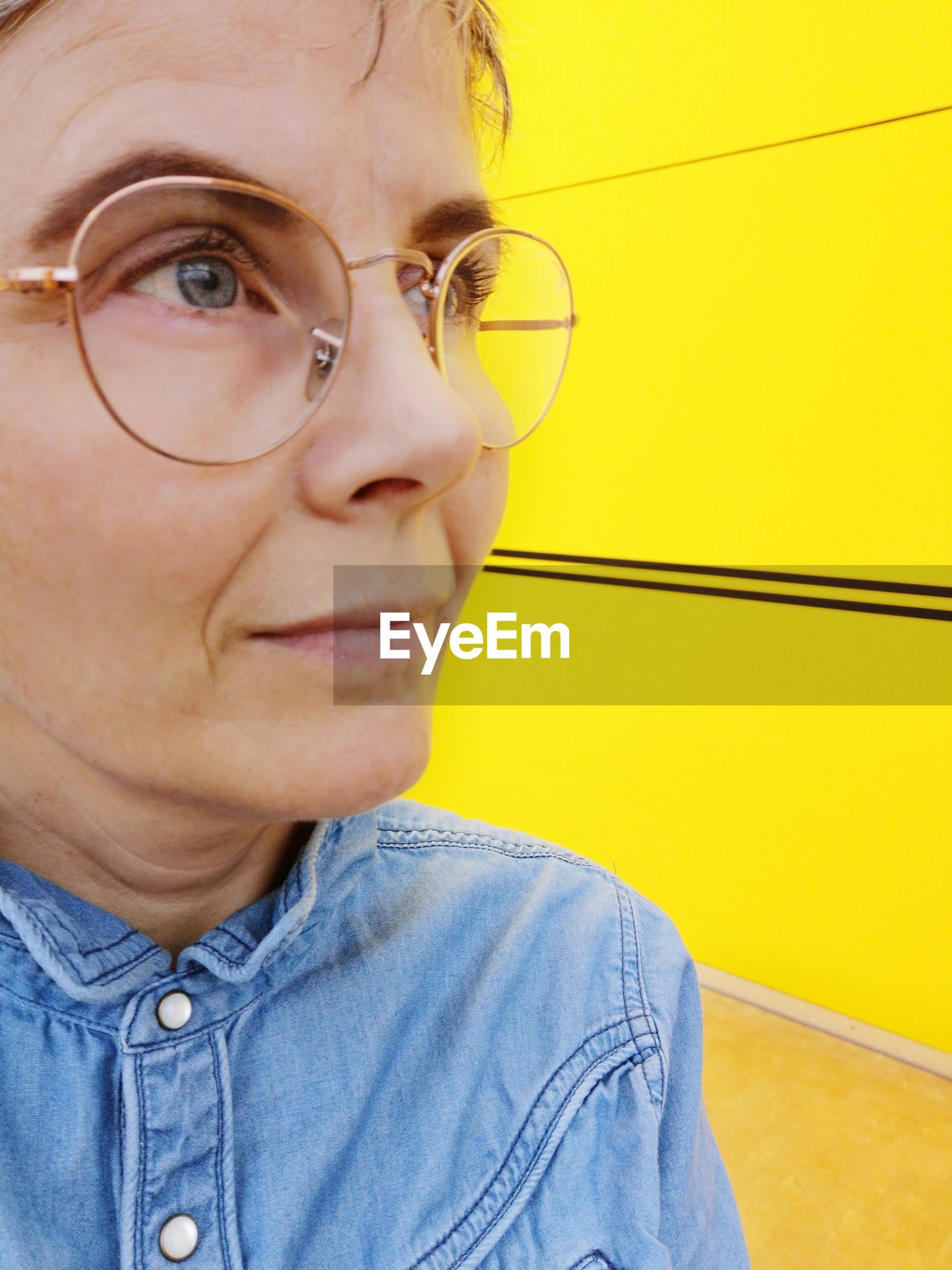 Close-up of thoughtful mature woman looking away while wearing eyeglasses