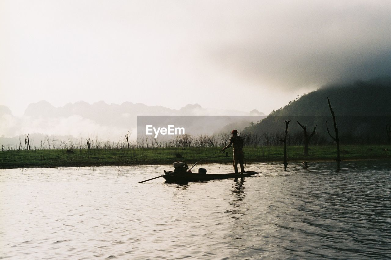 water, waterfront, real people, lifestyles, beauty in nature, men, transportation, mode of transportation, lake, sky, nature, nautical vessel, scenics - nature, non-urban scene, two people, fog, silhouette, people, leisure activity, outdoors, rowing, fisherman