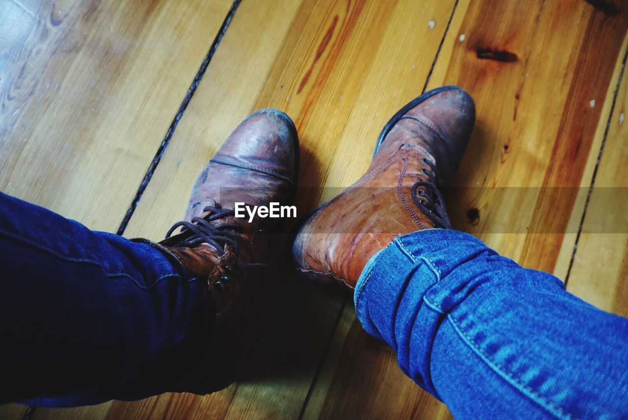 real people, personal perspective, low section, human leg, men, human body part, shoe, high angle view, wood, body part, wood - material, hardwood floor, indoors, one person, lifestyles, flooring, jeans, casual clothing, hand, human foot, human limb