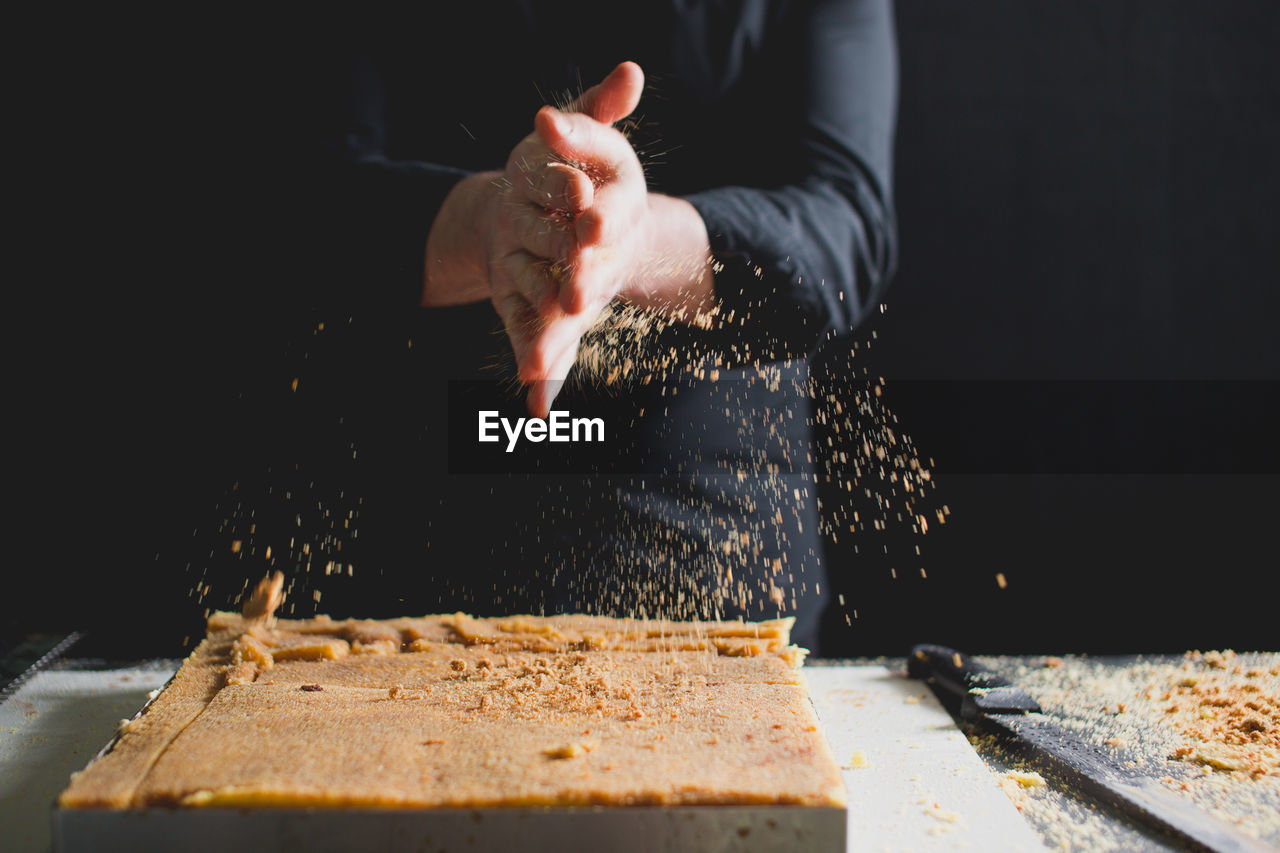 CLOSE-UP OF CHEF'S HANDS PREPARING SPONGE CAKE