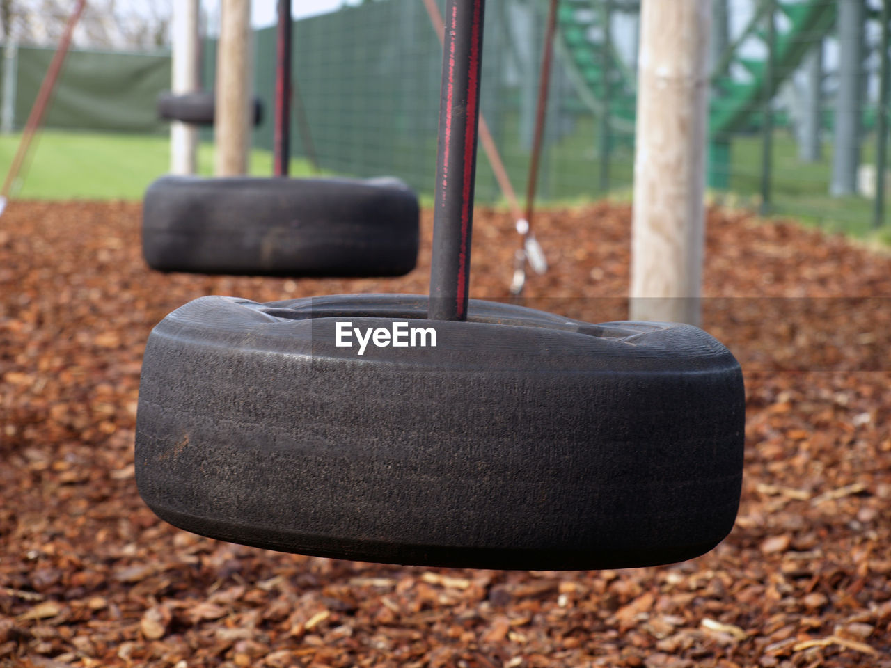focus on foreground, tree, day, nature, plant, land, playground, close-up, no people, outdoors, swing, seat, equipment, wheel, sport, absence, tire, hanging, solid, empty