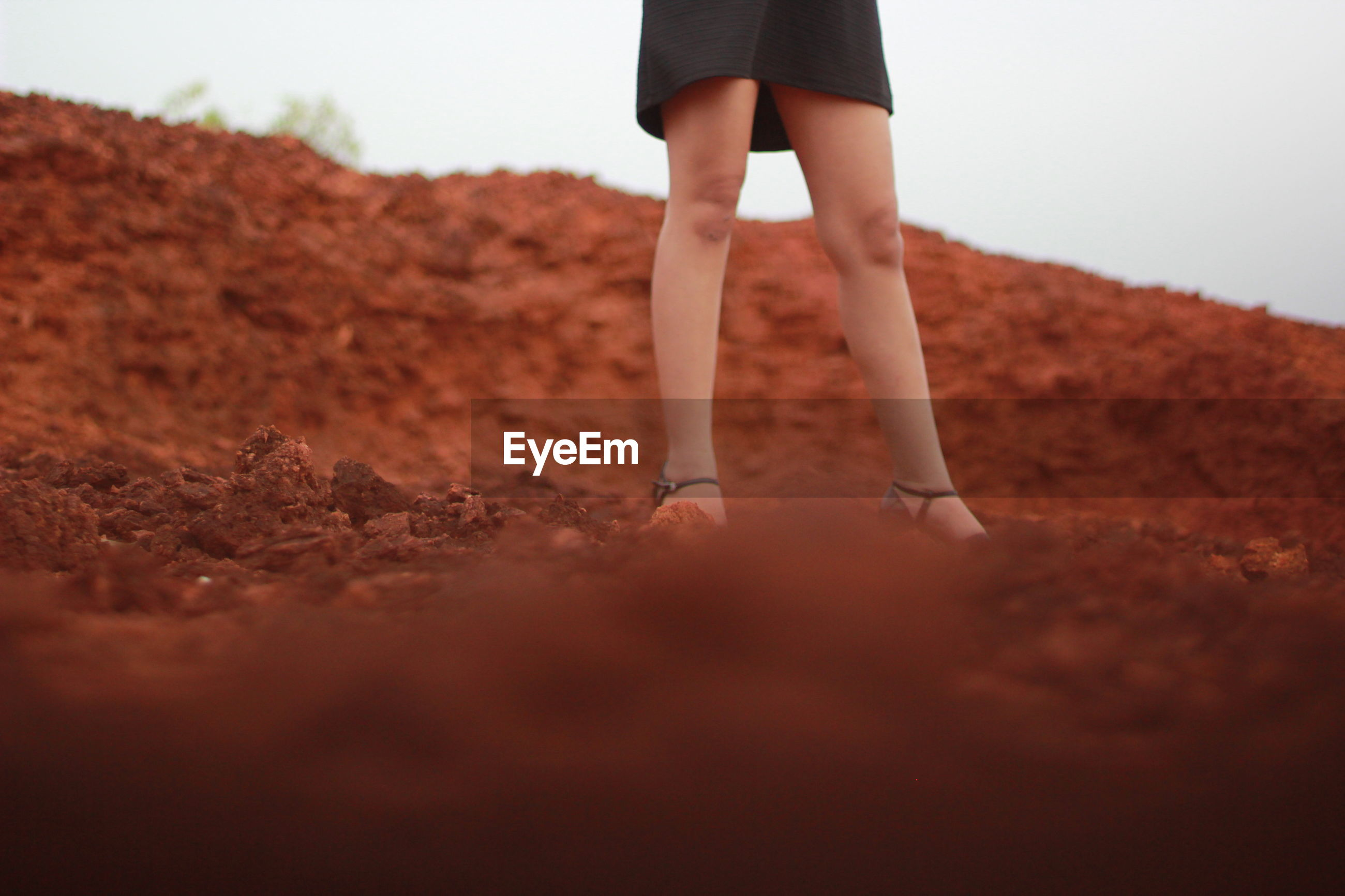 Low section of woman standing on sand