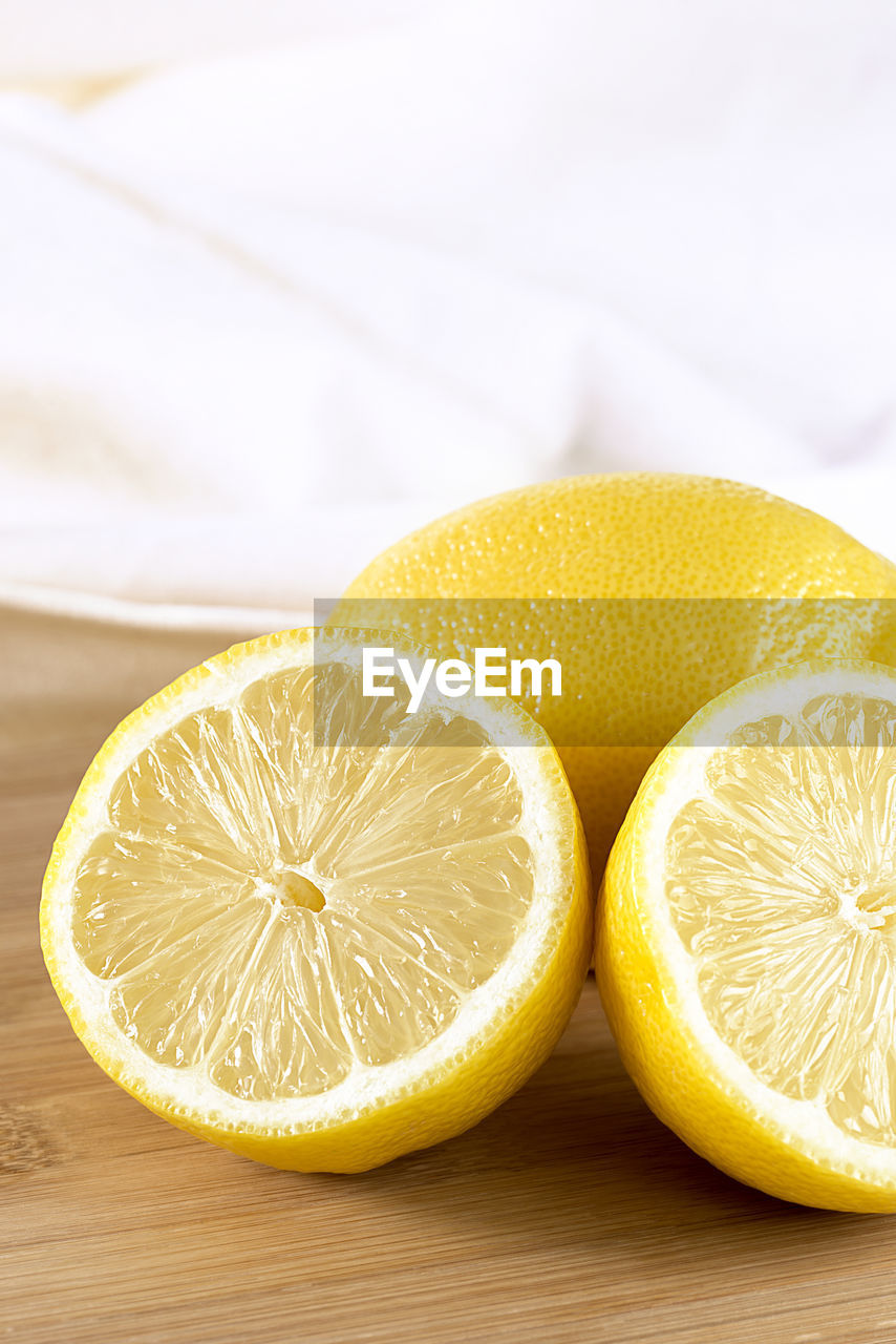 food and drink, fruit, healthy eating, food, freshness, wellbeing, still life, slice, citrus fruit, cross section, indoors, table, close-up, no people, yellow, halved, group of objects, focus on foreground, lemon, wood - material, orange