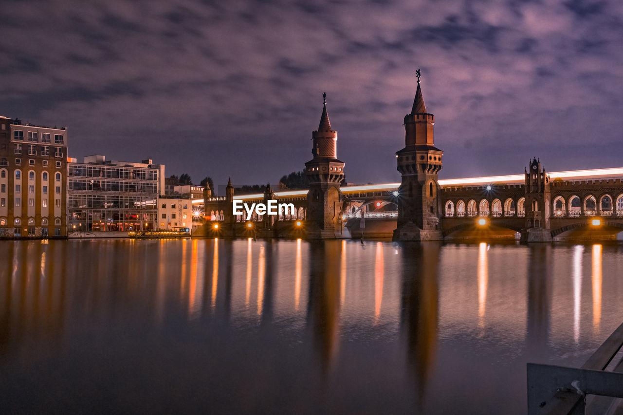 Illuminated oberbaum bridge over spree river against cloudy sky