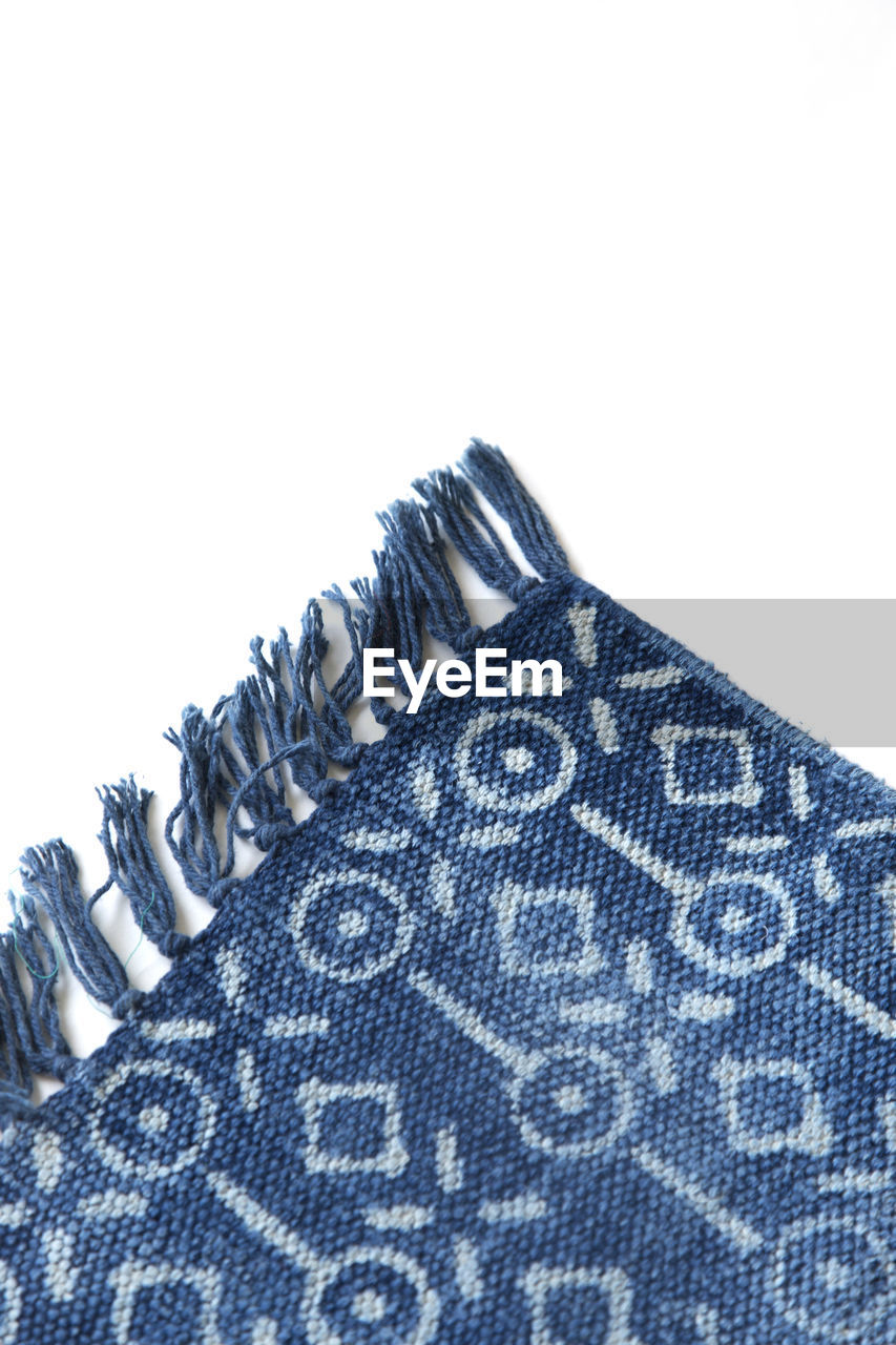 studio shot, white background, textile, close-up, indoors, metal, no people, pattern, still life, copy space, clothing, single object, cut out, casual clothing, blue, fashion, material, selective focus, silver colored, denim, jeans, garment, warm clothing
