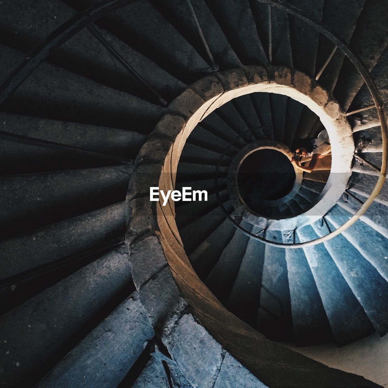 Woman Lying Down At Spiral Staircase