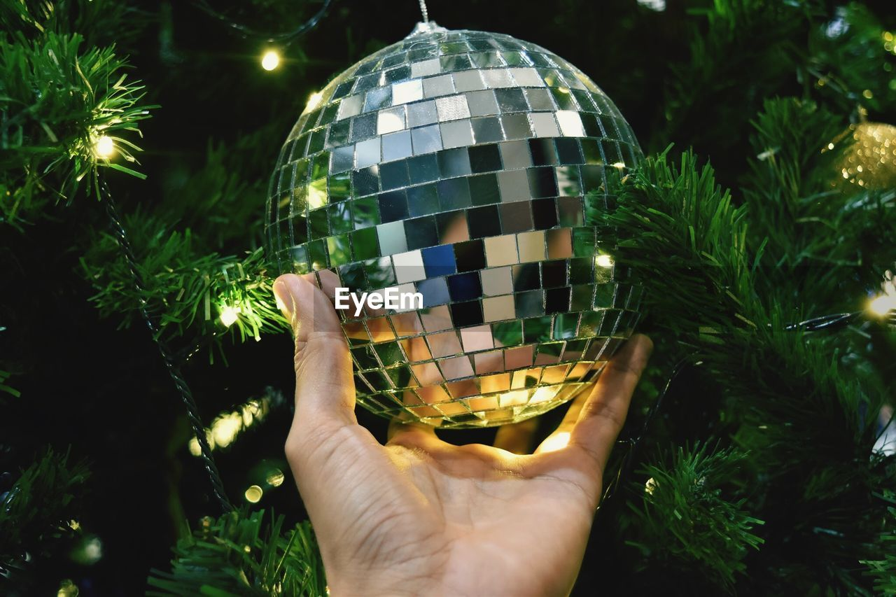 Close-up of hand holding disco ball on illuminated christmas tree at night