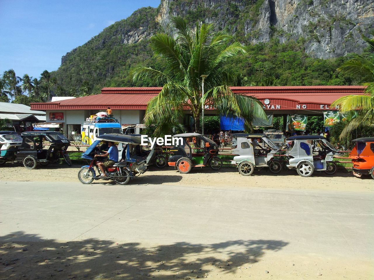 transportation, mode of transport, land vehicle, men, tree, real people, outdoors, day, sunlight, stationary, shadow, mountain, motorcycle, palm tree, architecture, sky, people