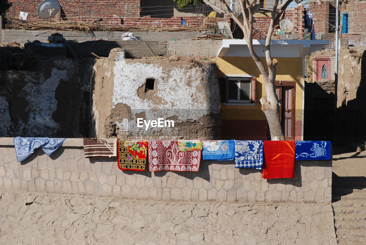 hanging, architecture, built structure, no people, multi colored, building exterior, drying, day, building, clothesline, wall - building feature, clothing, spirituality, textile, religion, sunlight, laundry, side by side, outdoors, belief