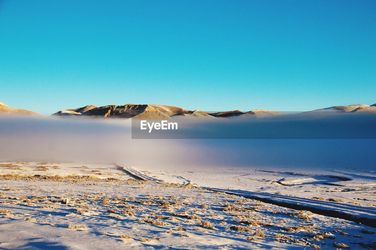 sky, tranquil scene, scenics - nature, beauty in nature, tranquility, winter, blue, snow, clear sky, mountain, copy space, cold temperature, non-urban scene, nature, no people, environment, landscape, idyllic, day, snowcapped mountain, climate, arid climate