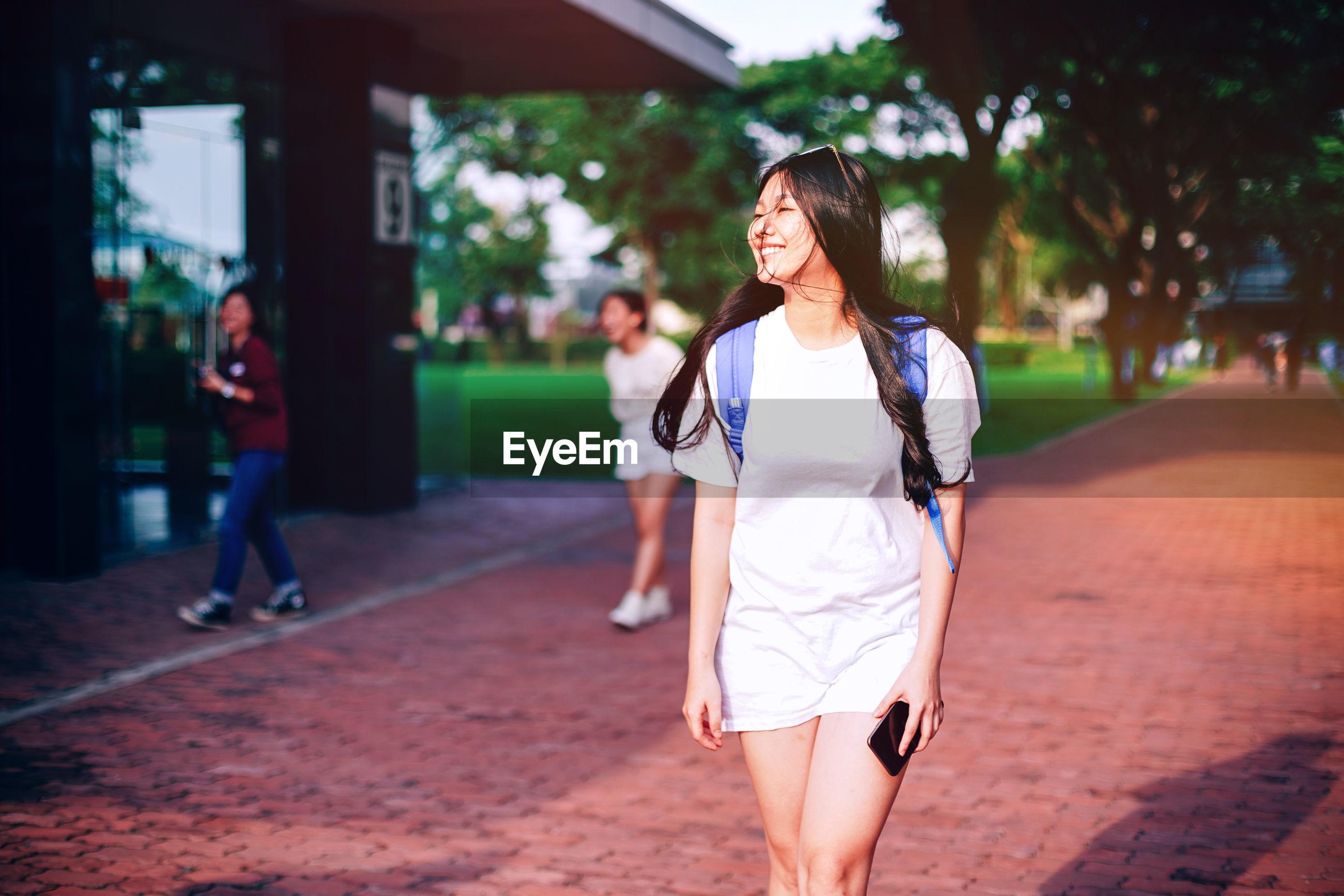 Smiling woman walking on footpath