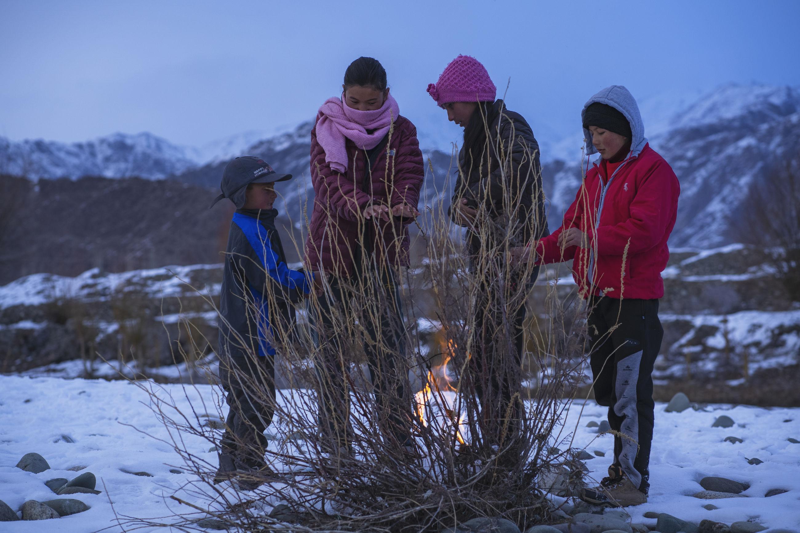 PEOPLE STANDING ON SNOWY FIELD