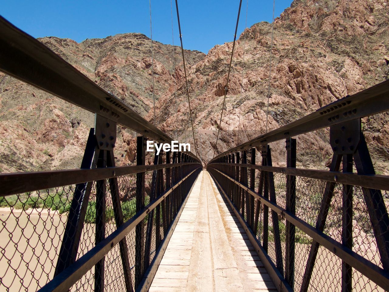connection, built structure, bridge, mountain, architecture, bridge - man made structure, nature, day, transportation, direction, the way forward, railing, sky, footbridge, no people, diminishing perspective, metal, outdoors, clear sky, tree