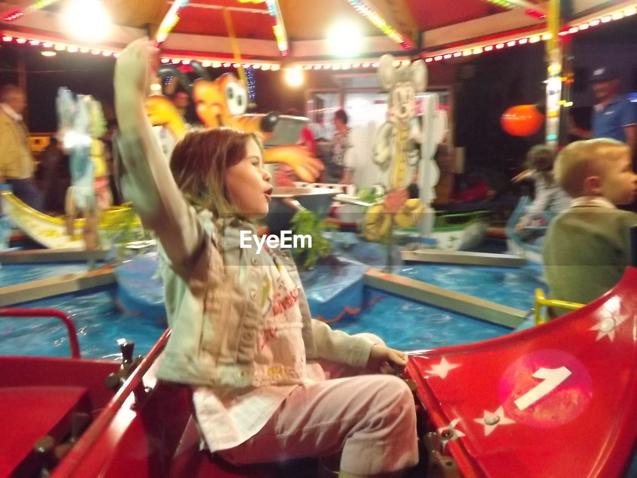 amusement park, amusement park ride, leisure activity, real people, carousel, enjoyment, arts culture and entertainment, incidental people, lifestyles, illuminated, casual clothing, sitting, ride, merry-go-round, night, outdoors, childhood, two people, happiness, young adult, people