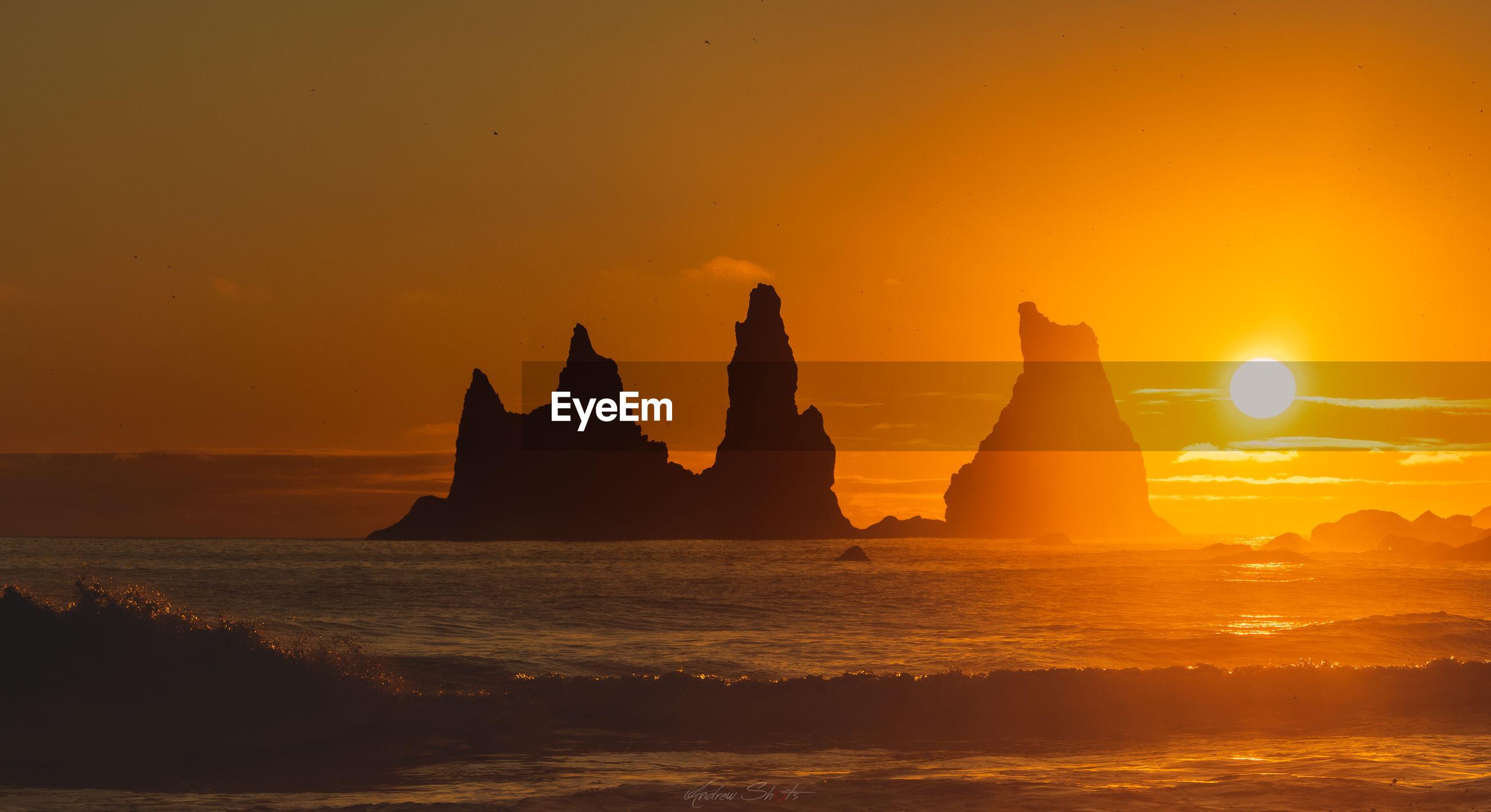 Silhouette rock formation in sea against orange sky