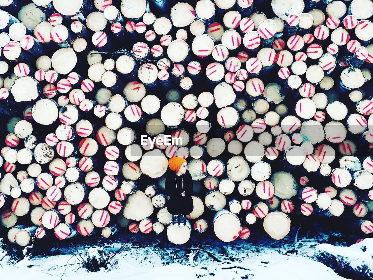 Woman Crouching Against Stacked Logs During Winter