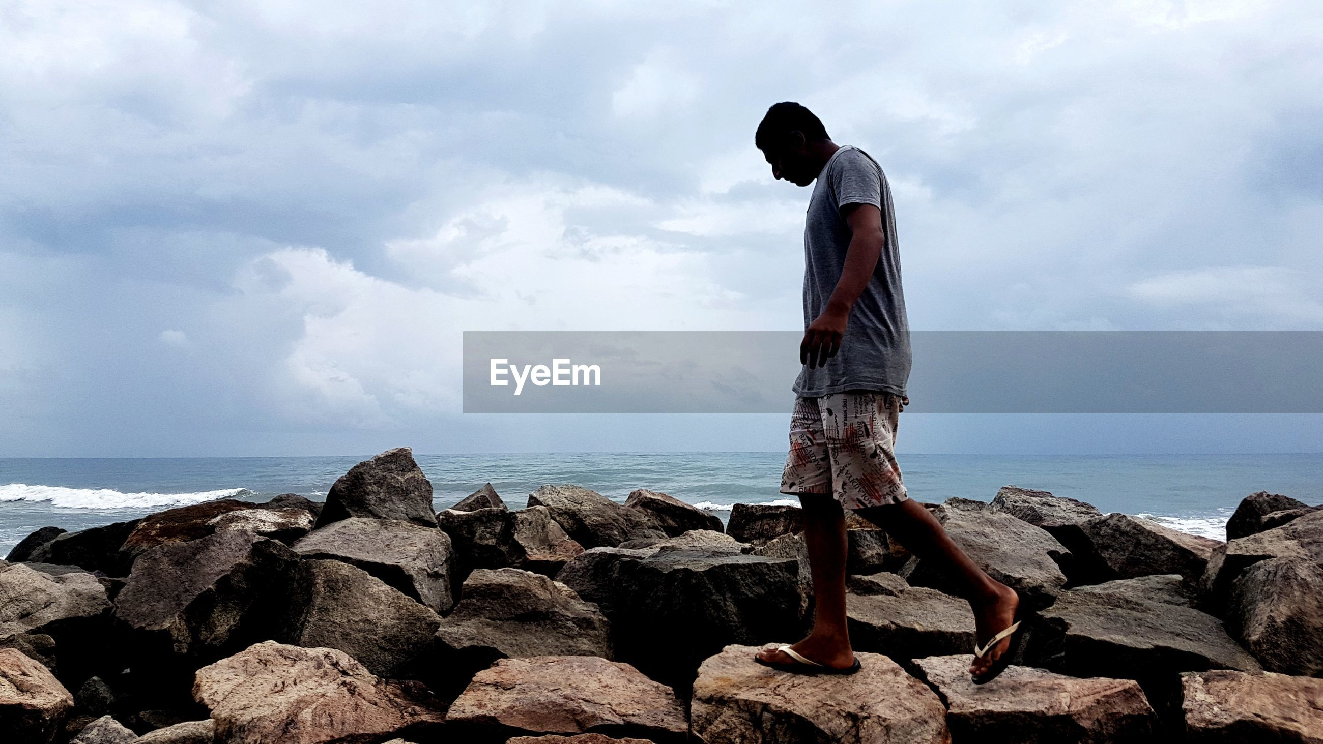 Side view of young man walking on rocks at beach against cloudy sky
