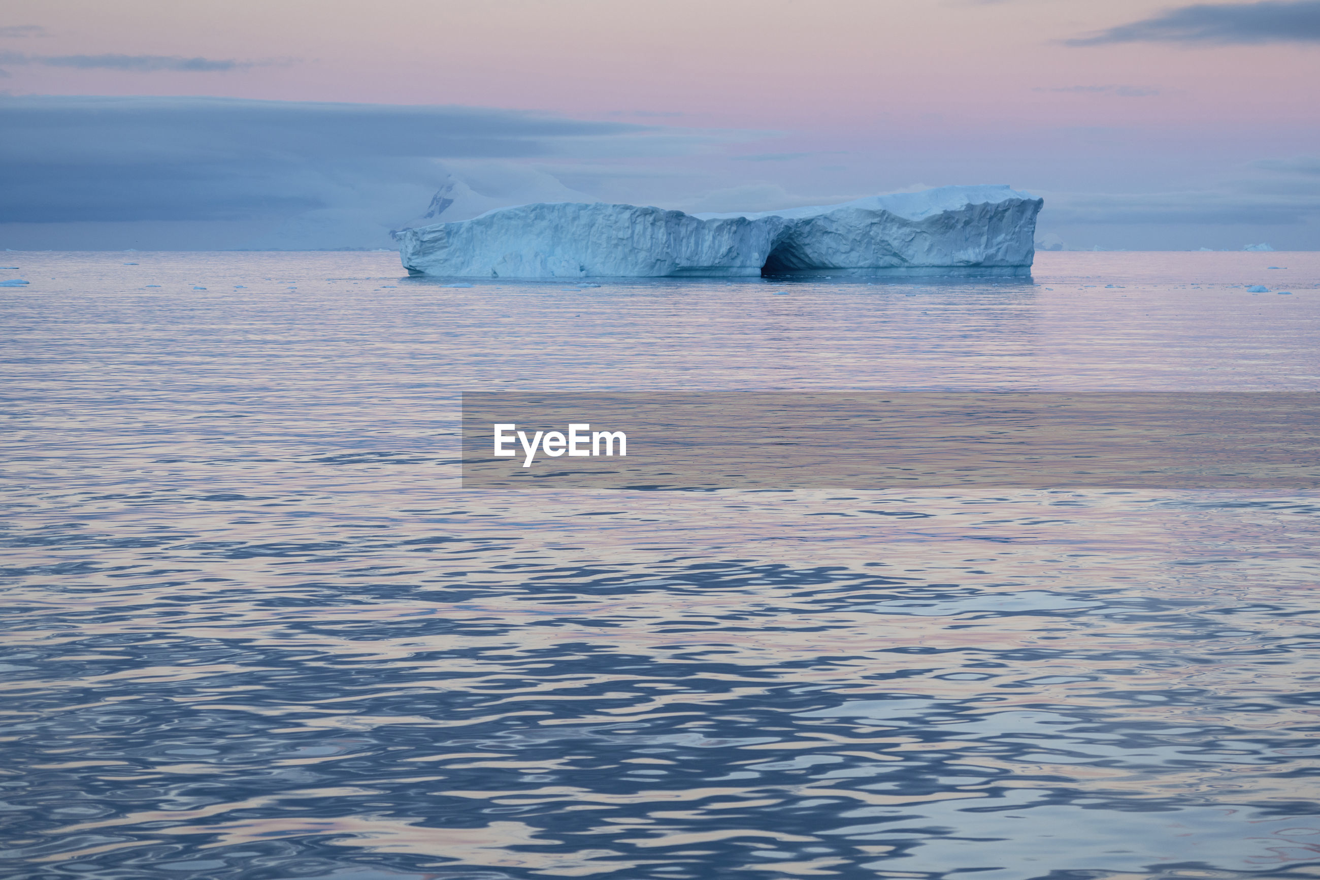 Scenic view of glacier in sea against sky during sunset