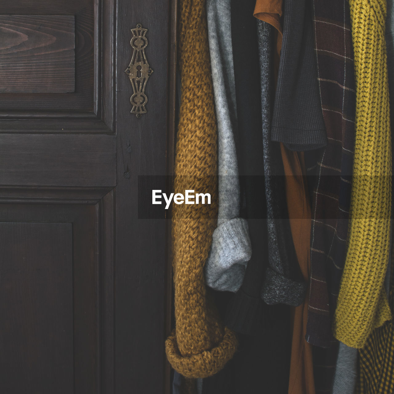 Close-Up Of Clothes Hanging By Wooden Door