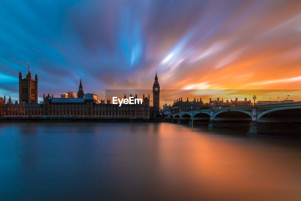 Bridge over river by big ben against cloudy sky during sunset