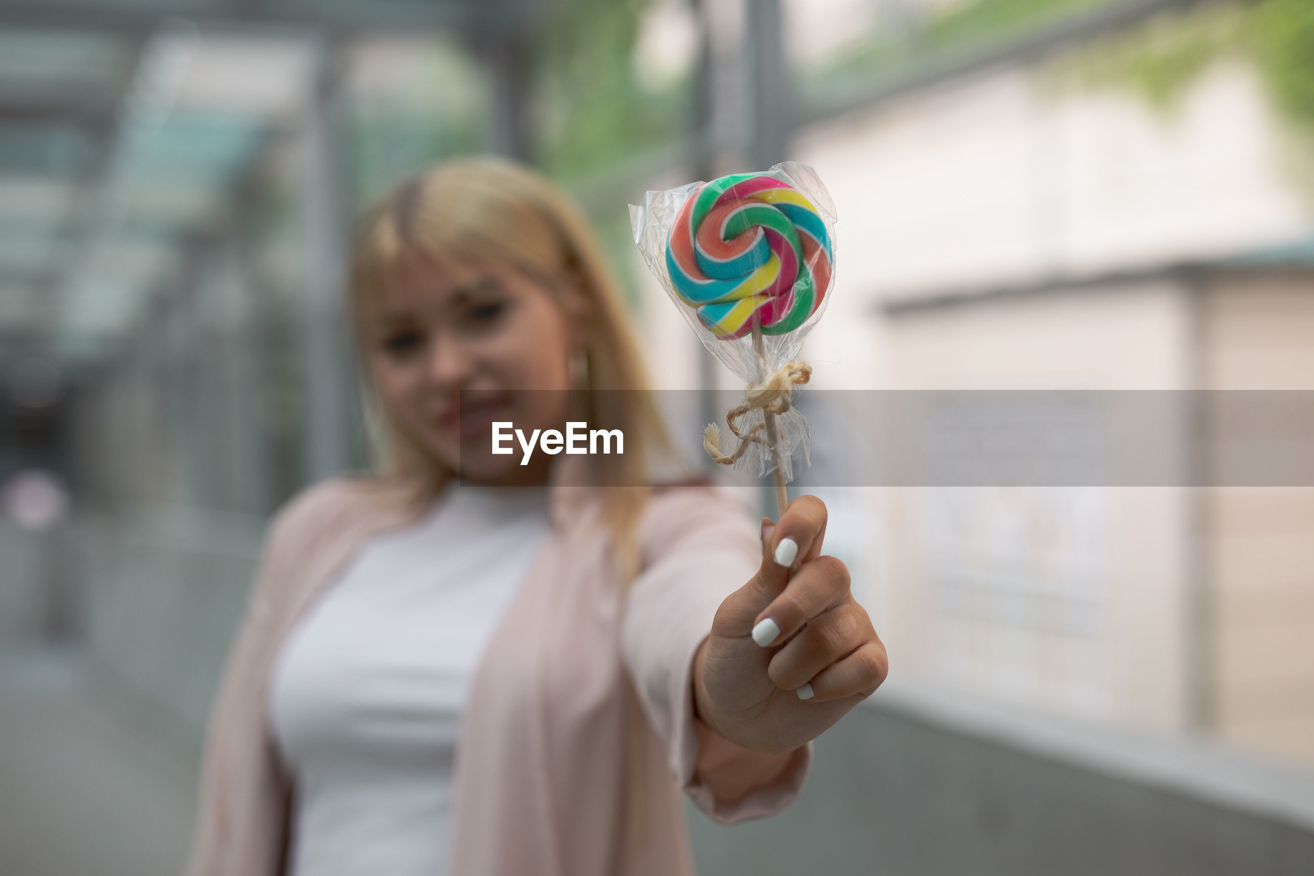 Young woman holding lollipop