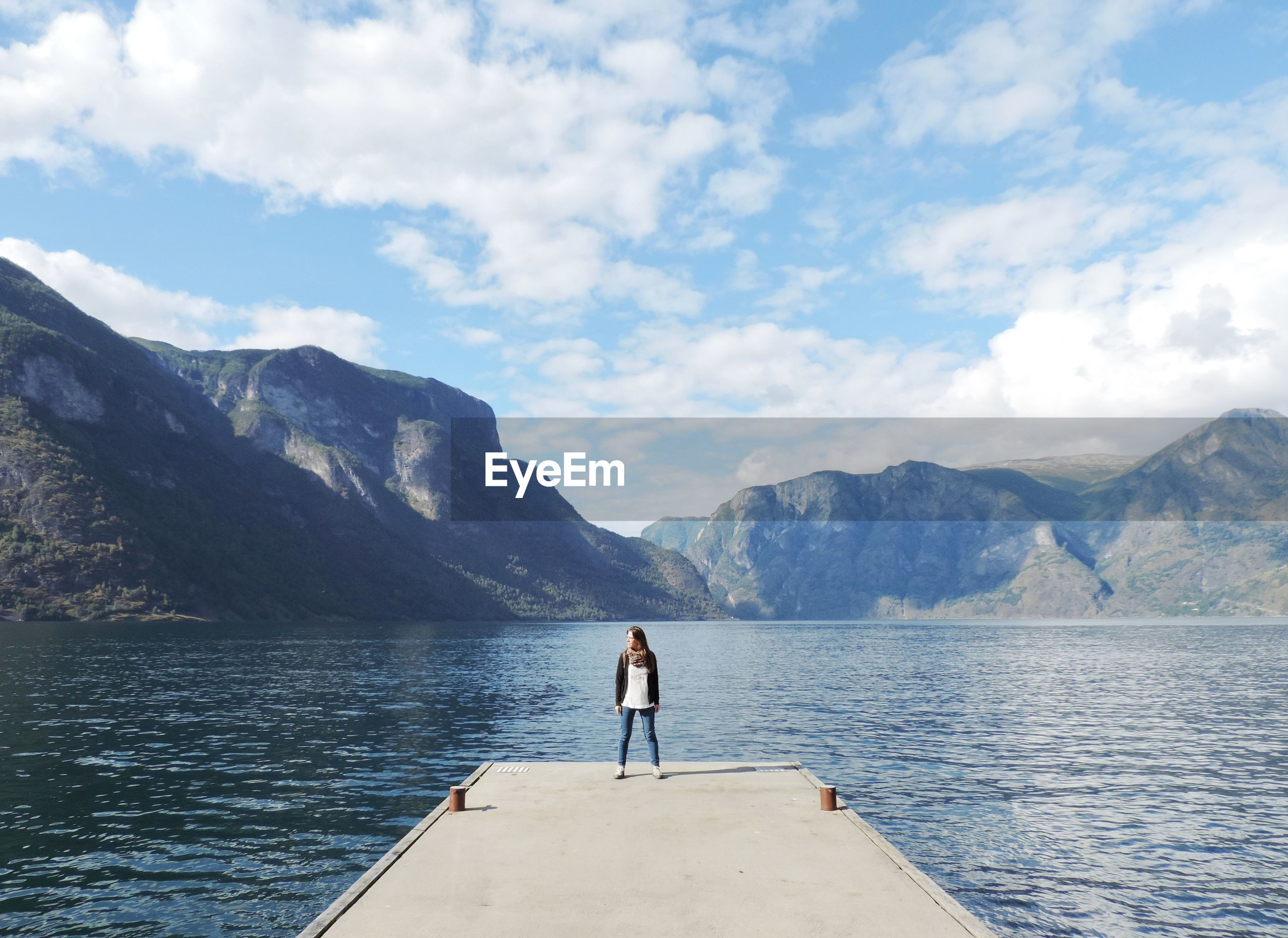 Woman standing on pier over lake against mountains