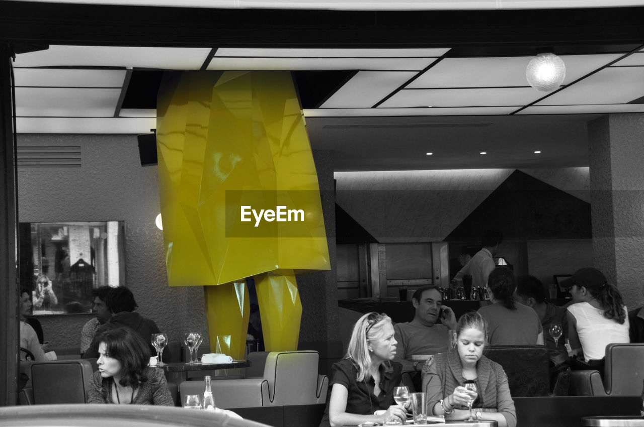 indoors, yellow, men, real people, togetherness, illuminated, women, architecture, day, people