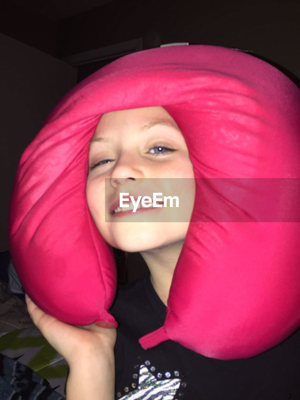 Close-up portrait of girl with pink neck pillow