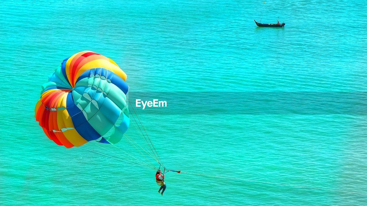 water, sea, adventure, real people, leisure activity, one person, blue, day, vacations, trip, nature, holiday, sport, paragliding, beauty in nature, lifestyles, waterfront, extreme sports, turquoise colored, outdoors, parasailing, inflatable, floating on water
