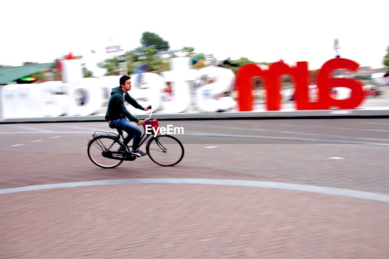 bicycle, mode of transport, transportation, cycling, riding, motion, land vehicle, blurred motion, real people, speed, full length, one person, outdoors, lifestyles, racing bicycle, men, road, day, cycling helmet, sky, people