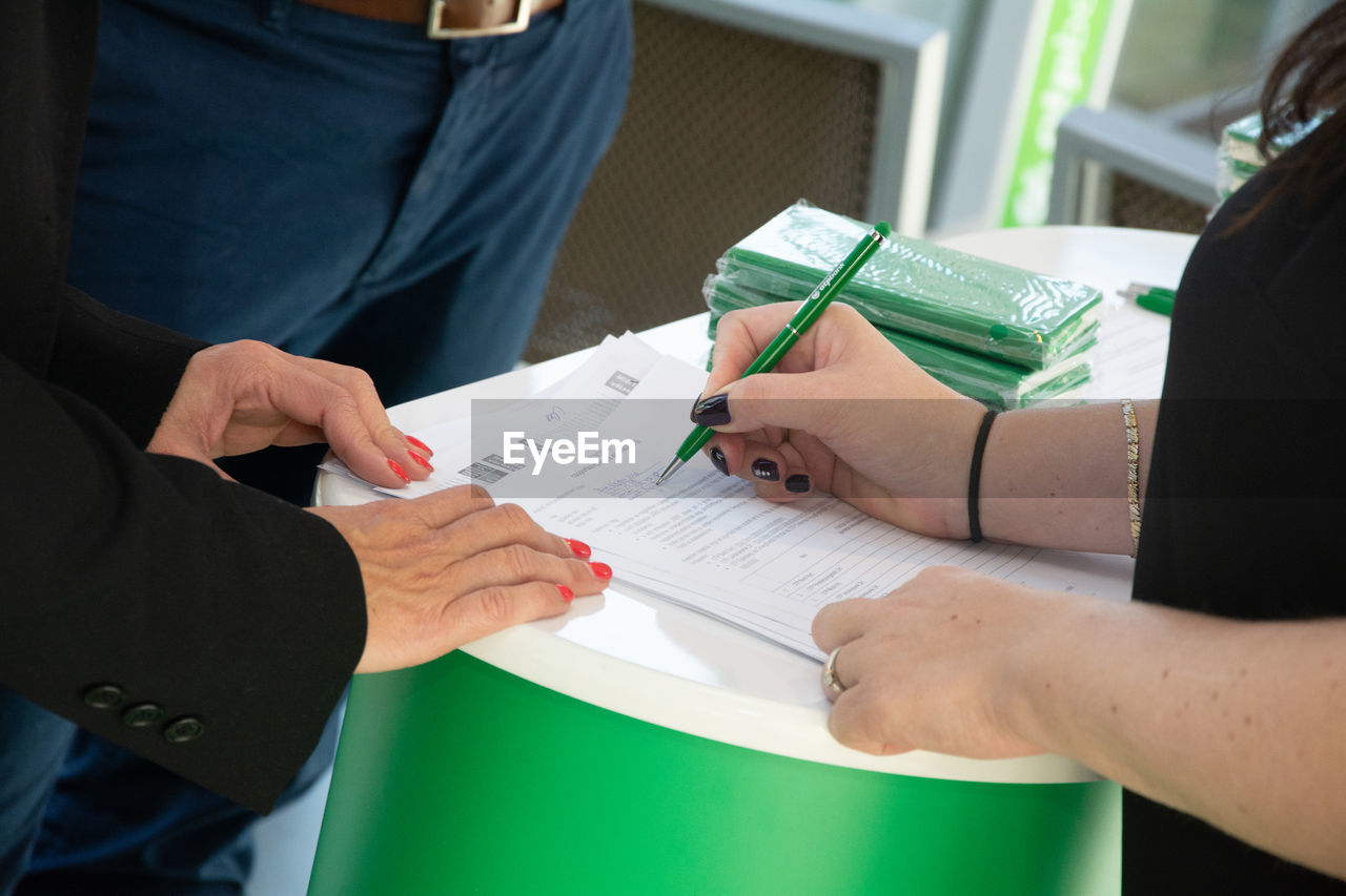 Midsection of colleagues filling form on table