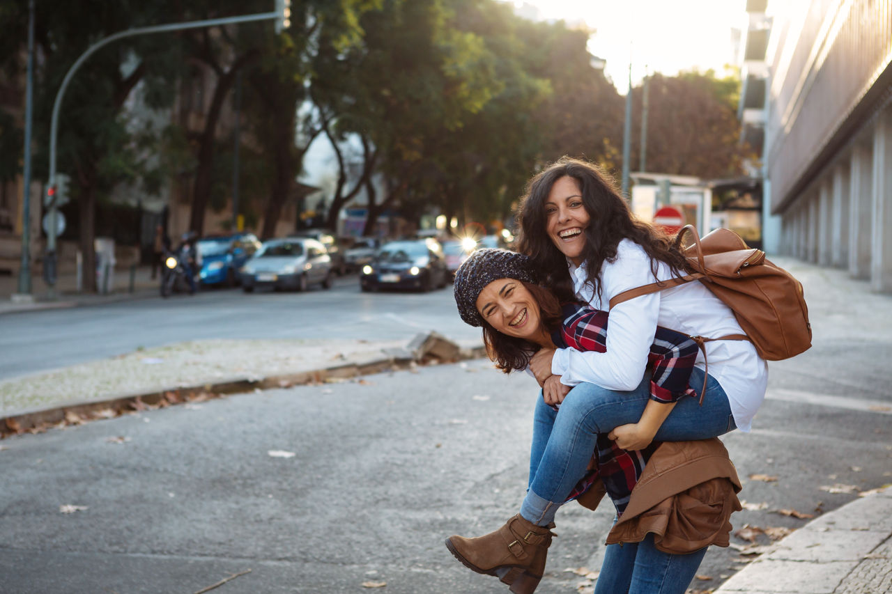 Happy Friends Playing On Street In City