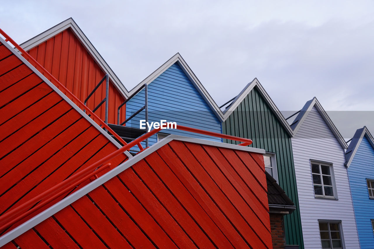 built structure, building exterior, architecture, red, sky, building, low angle view, no people, day, cloud - sky, nature, outdoors, pattern, house, roof, beach hut, multi colored, blue, residential district, side by side