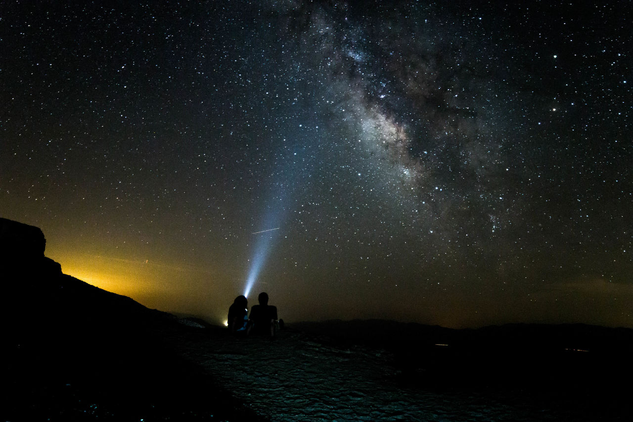 Silhouette Couple With Flashlight At Desert Against Star Field