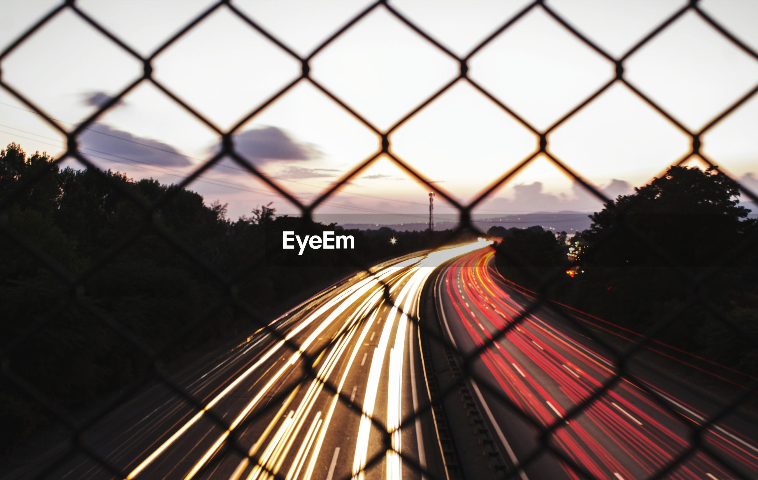 LIGHT TRAILS ON ROAD SEEN THROUGH CHAINLINK FENCE AGAINST SKY DURING SUNSET