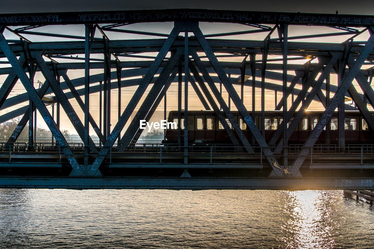 Train on railway bridge over river during sunset