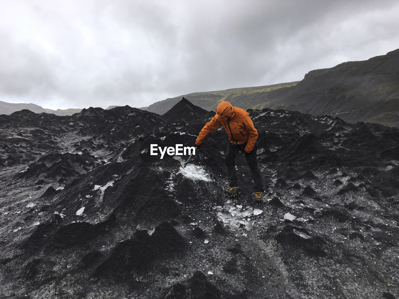 Man Breaking Ice On Mountain Against Cloudy Sky