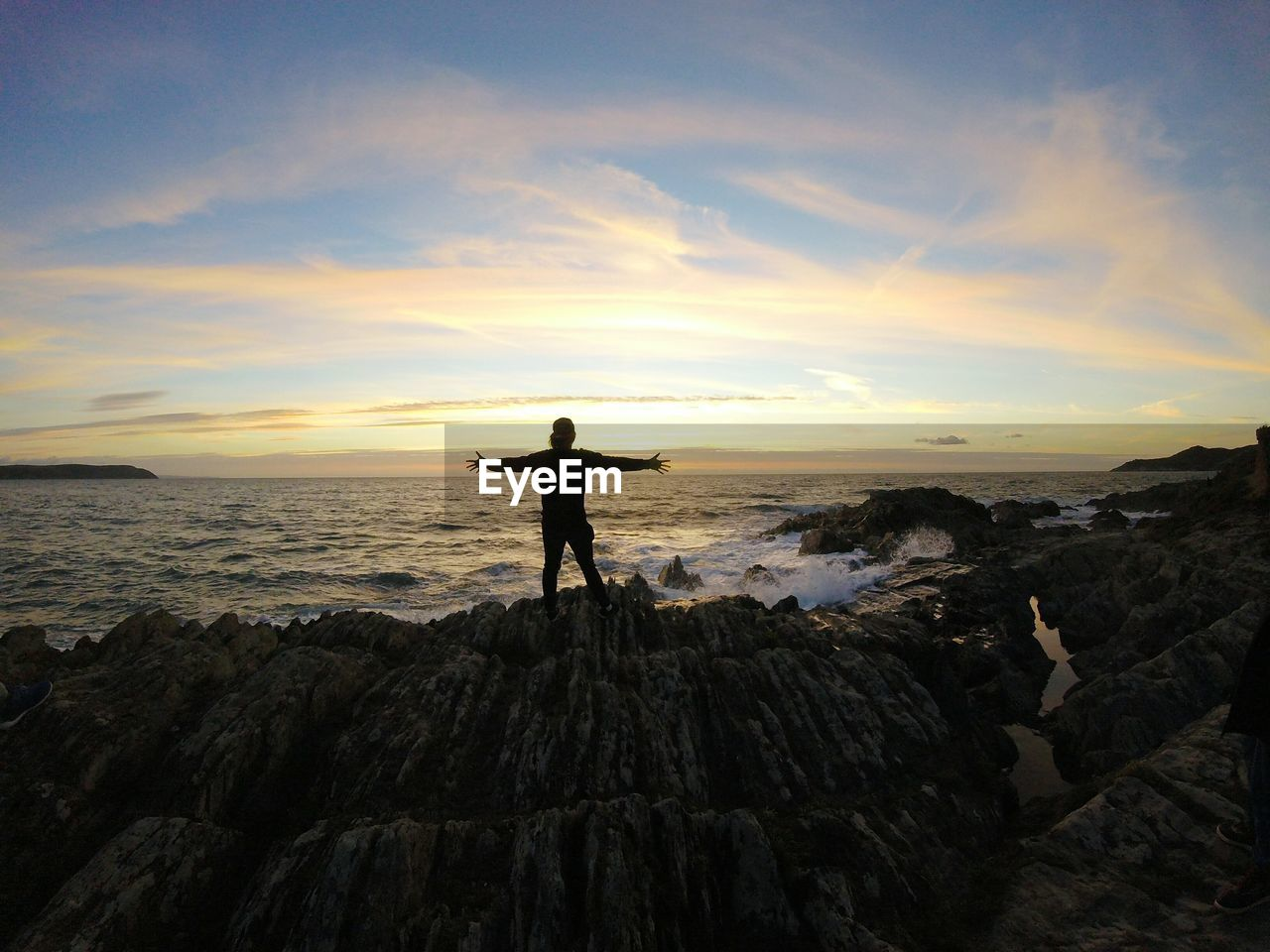 Rear view of man with arms outstretched standing on rock formation during sunset