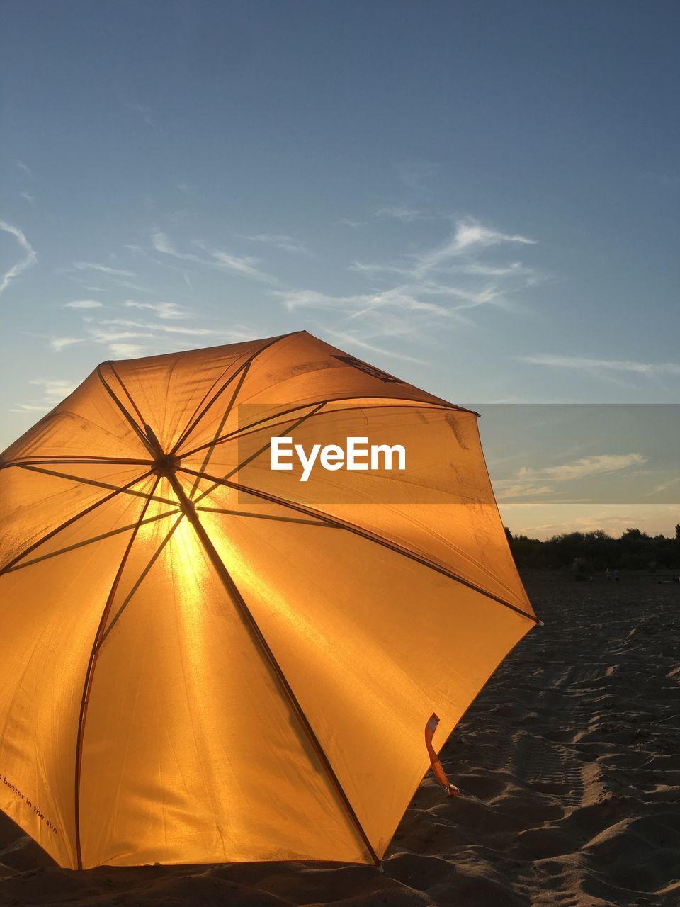 Umbrella On Sand Against Sky