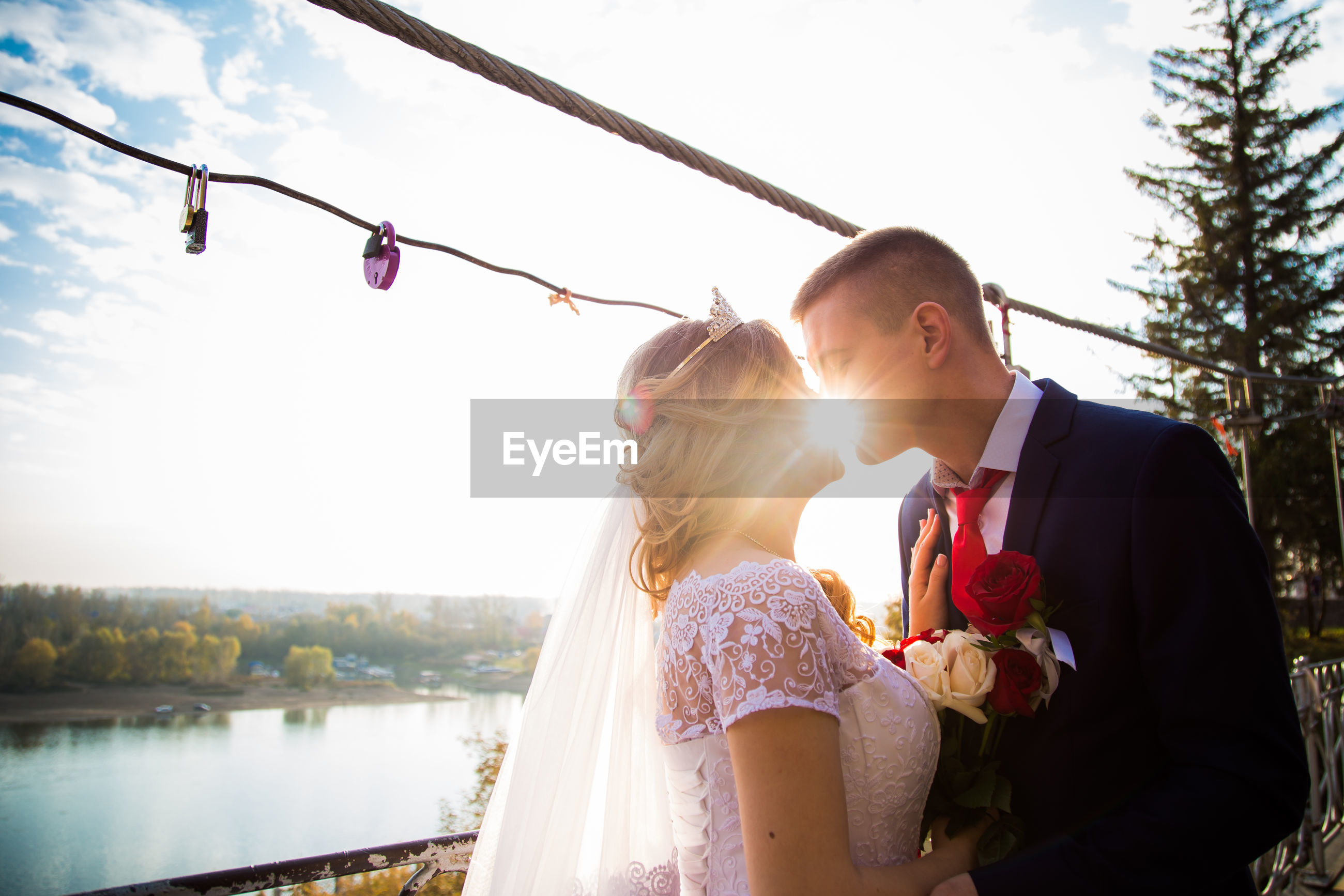 Couple kissing against lake and sky on sunny day