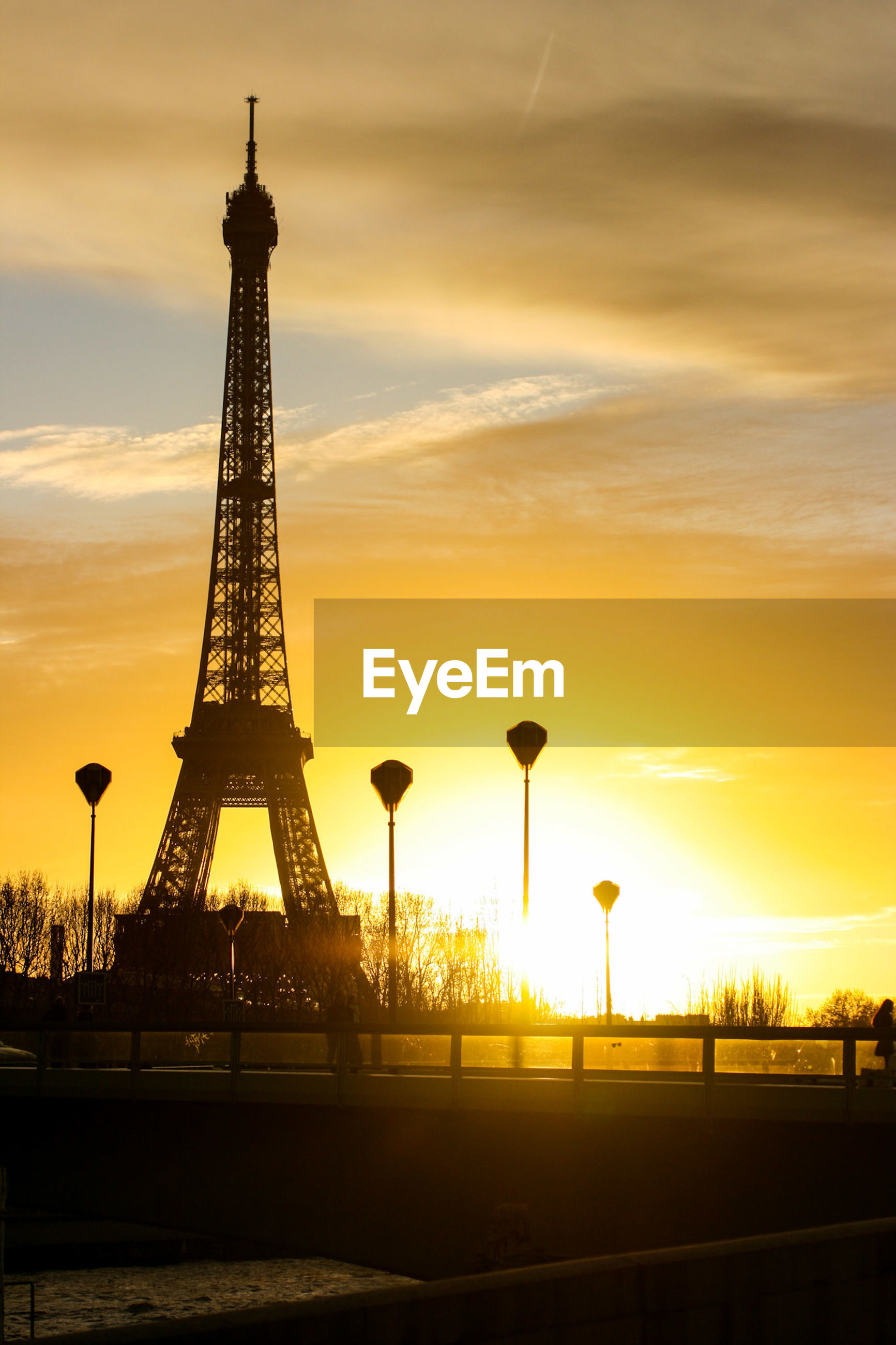 Silhouette eiffel tower against cloudy sky during sunset