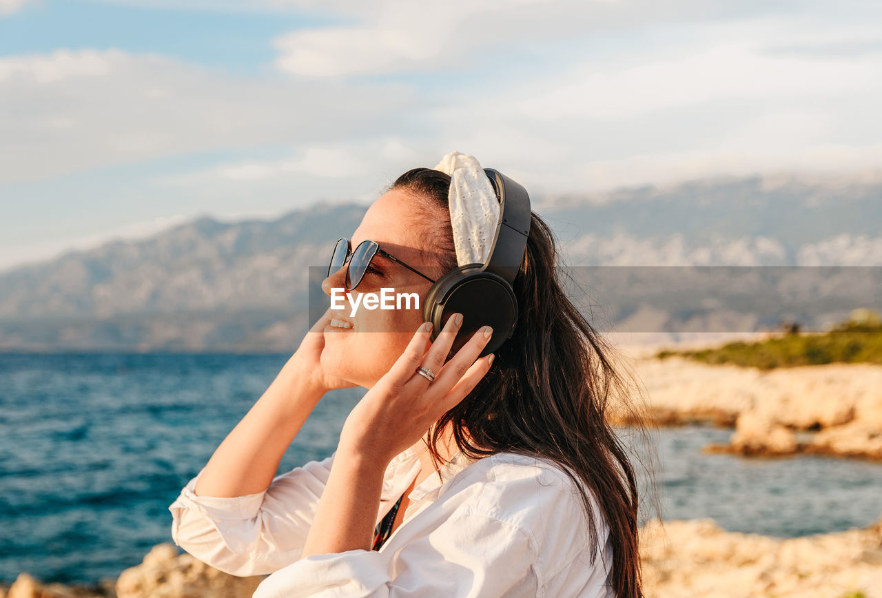 Young woman in white shirt listening to music on headphones. beach, summer, golden hour.