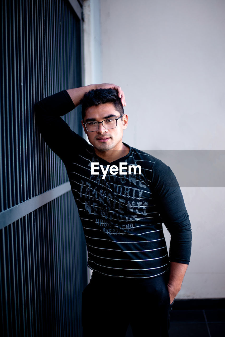 one person, young adult, front view, waist up, young men, real people, casual clothing, looking at camera, standing, indoors, glasses, wall - building feature, portrait, three quarter length, lifestyles, leisure activity, eyeglasses, striped