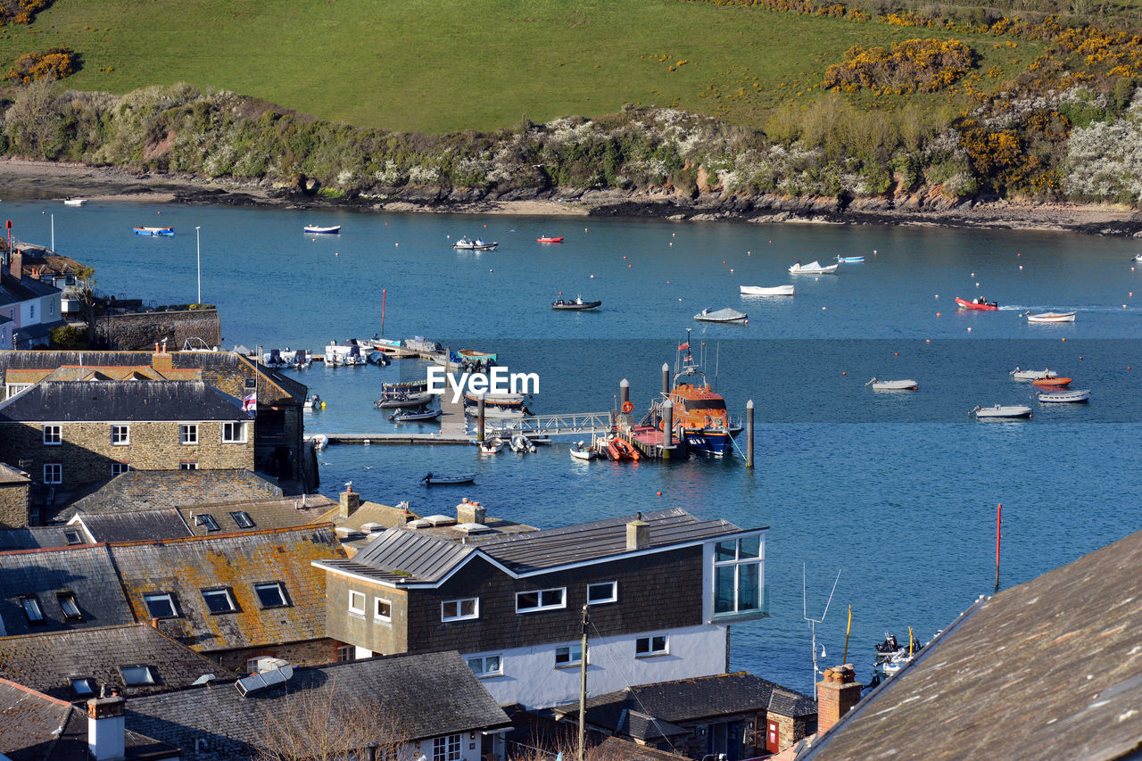 HIGH ANGLE VIEW OF SAILBOATS MOORED ON SEA BY BUILDINGS